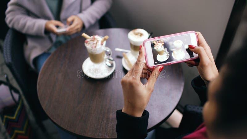 Closeupen av kvinnan räcker att fotografera kaffekoppen genom att använda smartphonen, medan sitta i gatakafé utomhus royaltyfria bilder