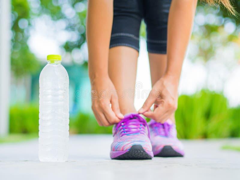 Closeupen av kvinnan som binder skon, snör åt Kvinnlig sportkonditionlöpare som får klar för att jogga med vattenflaskan arkivbild