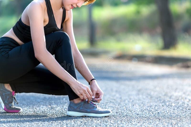 Closeupen av kvinnan som binder skon, snör åt Kvinnligt G för sportkonditionlöpare arkivfoton
