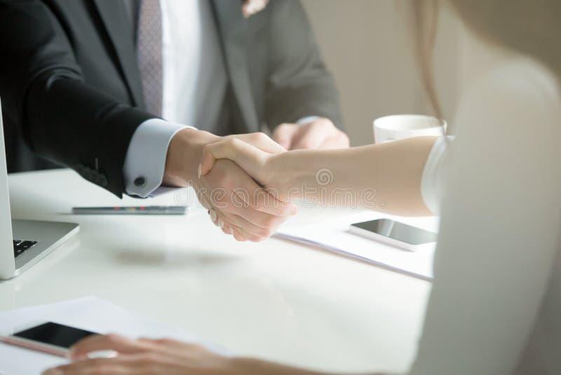 Closeupen av mannen och kvinnlign räcker handshaking efter effektiv negation royaltyfri foto