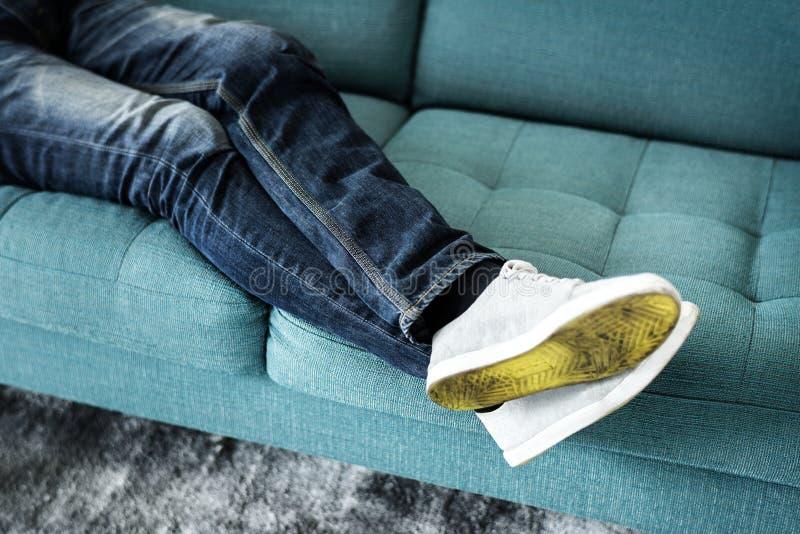 Closeupen av person` s lägger benen på ryggen sammanträde på soffan royaltyfri foto