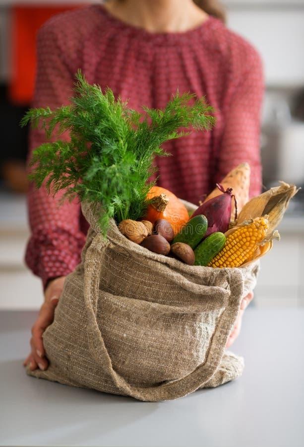 Closeupen av säckvävsäcken fyllde med nedgånggrönsaker med kvinnan arkivbilder