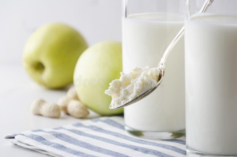 Closeupen av skeden med keso mot exponeringsglas av mjölkar, äpplet, muttrar Begrepp av den sunda livsstilen, hälsokost royaltyfria foton