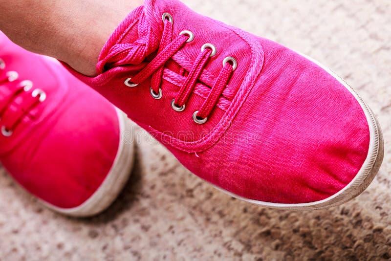 Closeupen av tillfälliga vibrerande rosa gymnastikskor skor kängor på kvinnlig fot royaltyfri bild