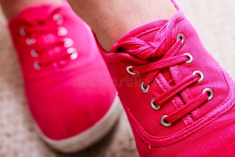 Closeupen av tillfälliga vibrerande rosa gymnastikskor skor kängor på kvinnlig fot arkivbilder