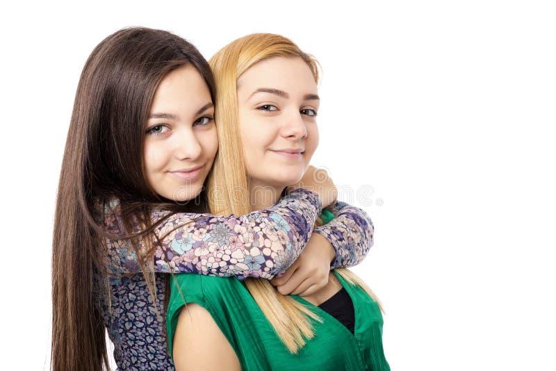Closeupen av två isolerade systrar kramar att ha gyckel royaltyfri fotografi