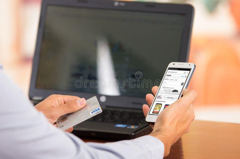 Closeupen av ungt mans händer som rymmer upp smartphonen arkivfoto
