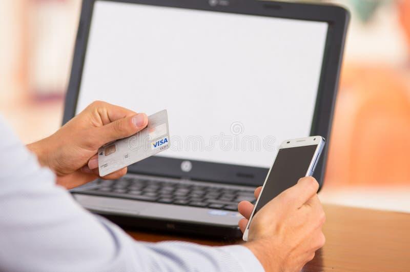 Closeupen av ungt mans händer som rymmer upp smartphonen royaltyfri fotografi