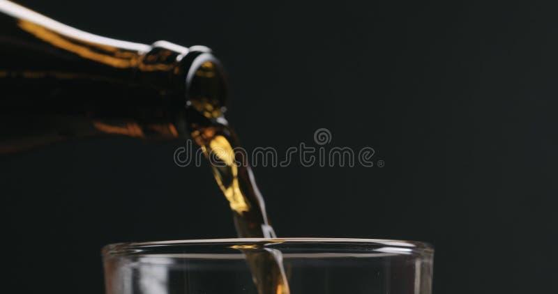 Closeupen häller mörkt öl från den bruna flaskan in i exponeringsglas på svart bakgrund fotografering för bildbyråer