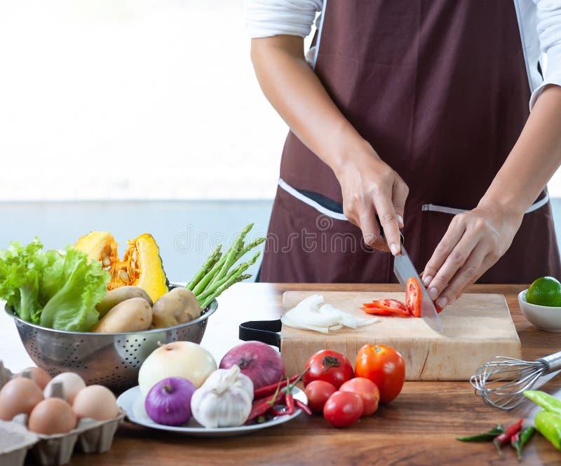 Closeupen kockens hand skivar grönsaker på en träskärbräda med en kniv på köksbordet fyllde med grönsaker arkivbilder