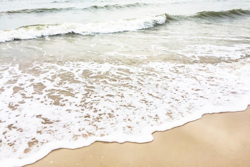 Closeupen på sandstranden och havet vinkar på molnig dag arkivbilder