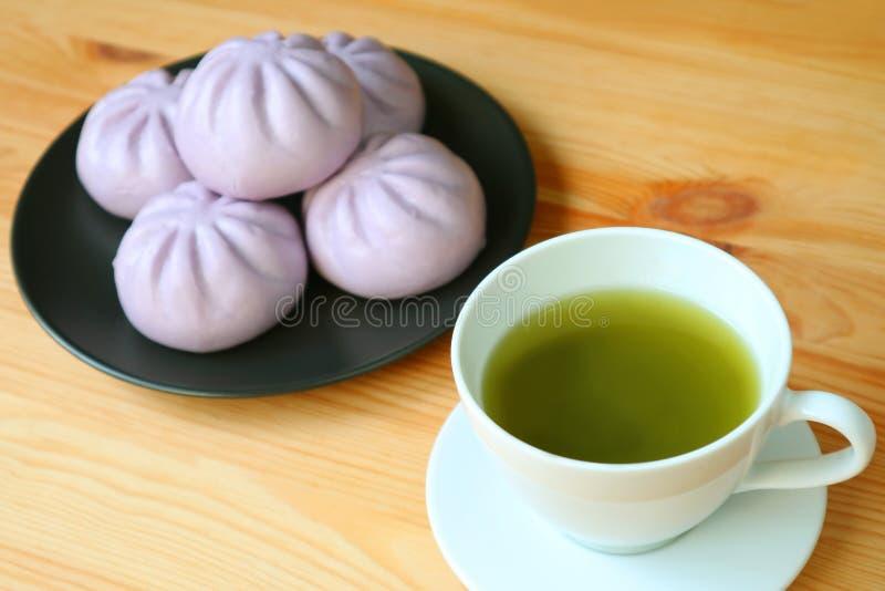 Closeupen per koppen av grönt te med den oskarpa högen av den purpurfärgade sötpotatisen ångade bullar på trätabellen arkivbilder