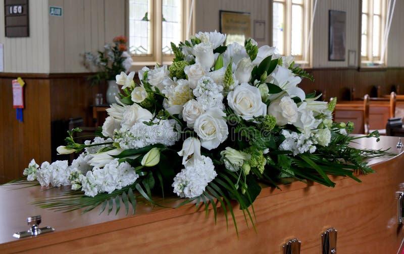 Closeupen sköt av en färgrik casket i en likvagn eller kapell för begravning eller jordfästning på kyrkogården fotografering för bildbyråer