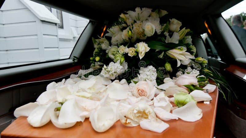 Closeupen sköt av en färgrik casket i en likvagn eller kapell för begravning eller jordfästning på kyrkogården arkivfoton