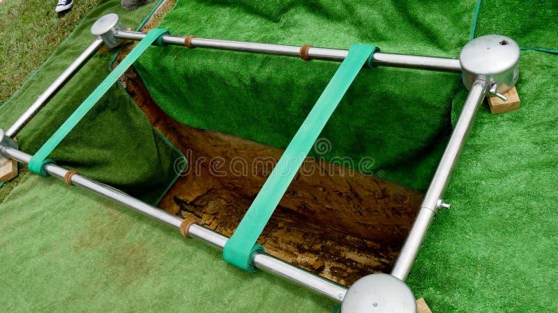 Closeupen sköt av en färgrik casket i en likvagn eller kapell för begravning eller jordfästning på kyrkogården royaltyfri fotografi