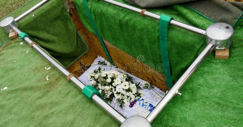 Closeupen sköt av en färgrik casket i en likvagn eller kapell för begravning eller jordfästning på kyrkogården arkivbilder