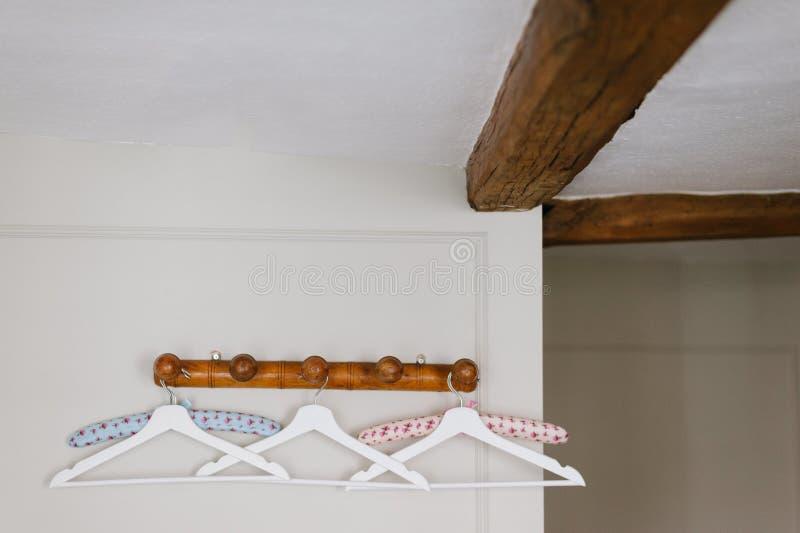 Closeupen sköt av en samling av hängare på en trästång på en vit vägg arkivfoton