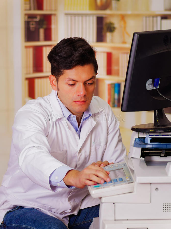 Closeupen sköt den unga manliga teknikeren som testar den digitala fotokopiatormaskinen, efter det fås fast arkivfoton