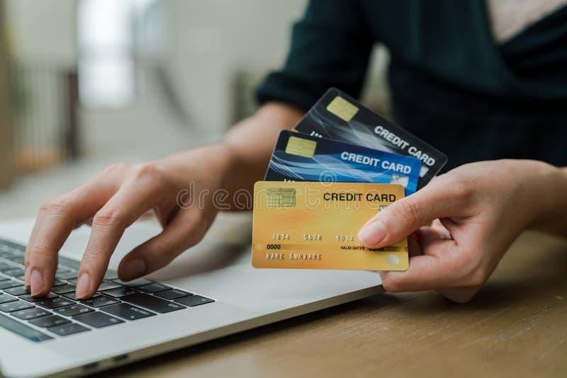 Closeupen som den asiatiska härliga kvinnan som bär en svart skjorta som sitter i huset, har en kreditkort i hand, köper online-p arkivfoton