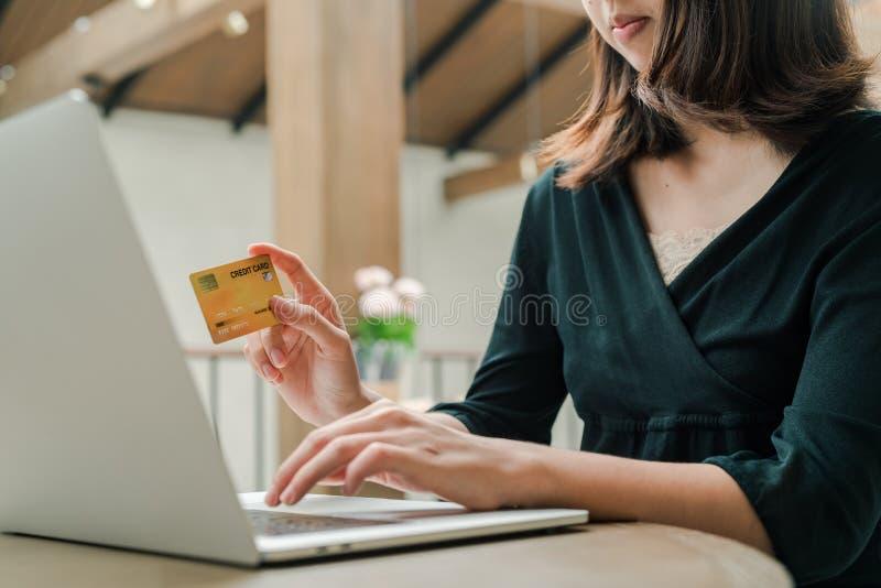 Closeupen som den asiatiska härliga kvinnan som bär en svart skjorta som sitter i huset, har en kreditkort i hand, köper online-p arkivbilder