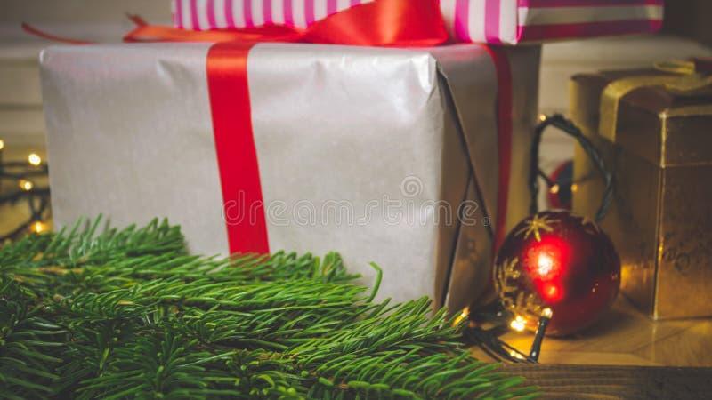 Closeupen tonade bild av den stora gåvaasken med det röda bandet på trätabellen bredvid julpynt arkivfoton