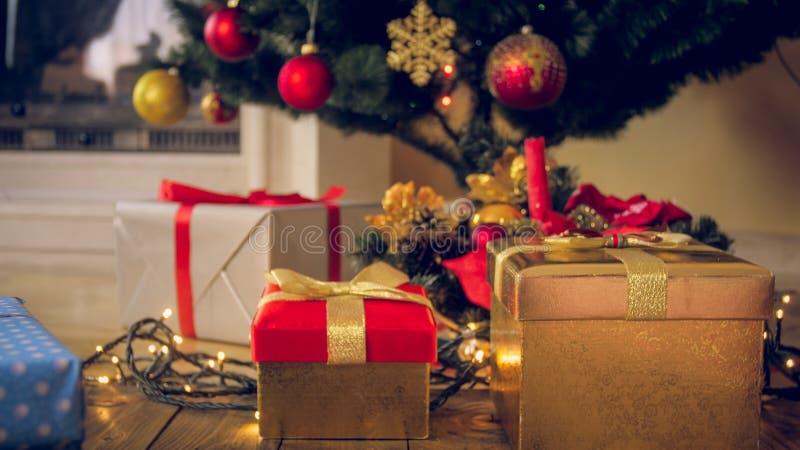 Closeupen tonade bild av färgrika gåvor och gåvor i askar under julgranen på vardagsrum royaltyfri fotografi