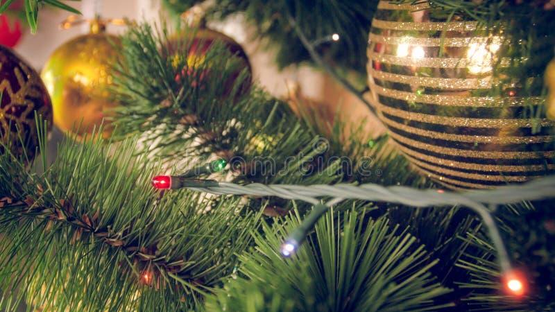 Closeupen tonade bild av färgrika ljusa girlander och struntsaker på julgranen royaltyfri fotografi