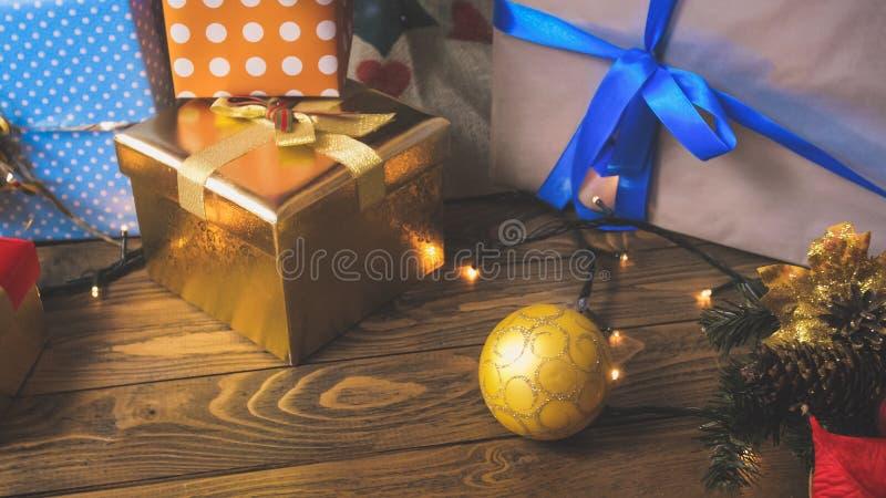 Closeupen tonade bild av struntsaker, glödande ligthgirlander och julgåvor på träskrivbordet royaltyfri foto
