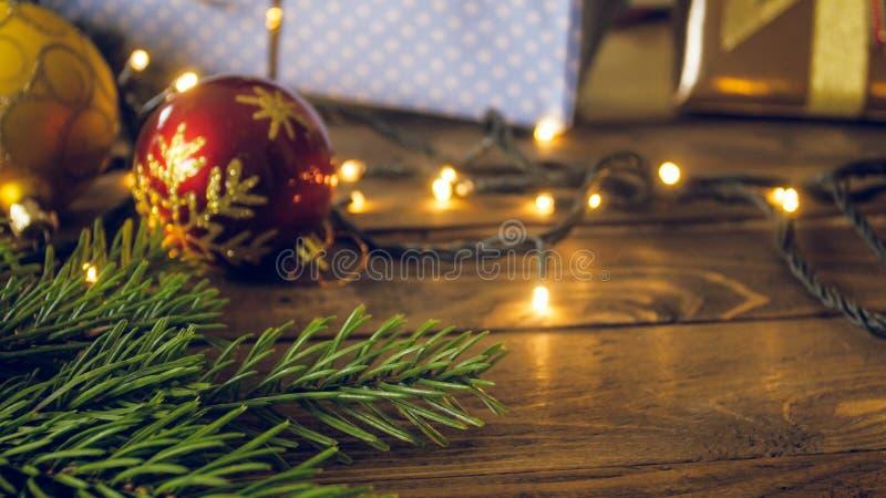 CLoseupen tonade fotoet av den röda struntsaken, glödande ljusa girlander och granträdfilialen som ligger på träbakgrund royaltyfri fotografi