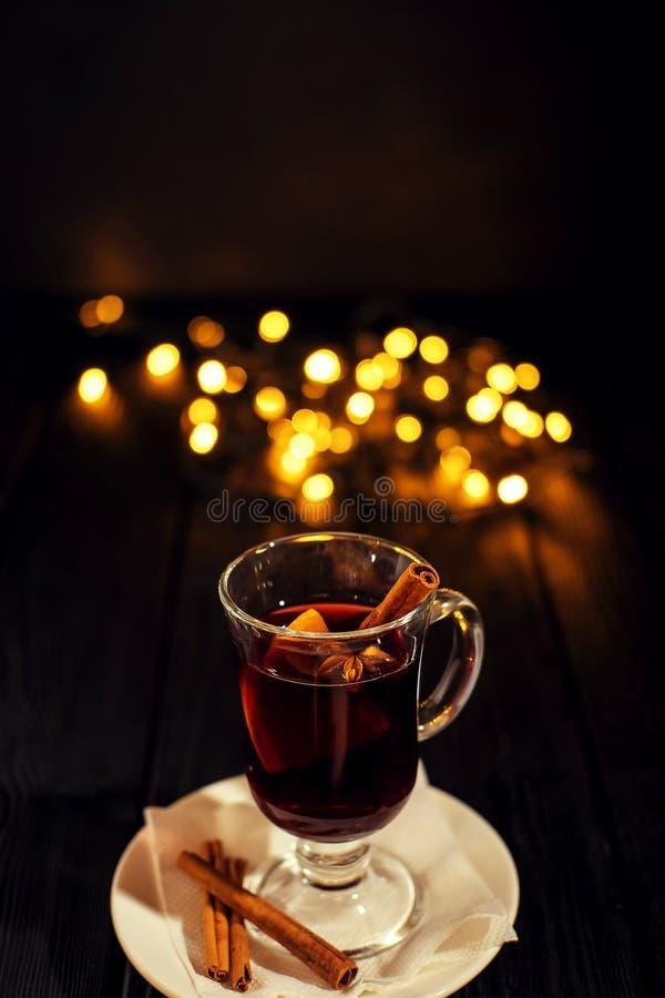 Closeupexponeringsglas av funderat vin med orange och kanelbrunt på mörk svart bakgrund, på den vita plattan, julljus royaltyfri bild