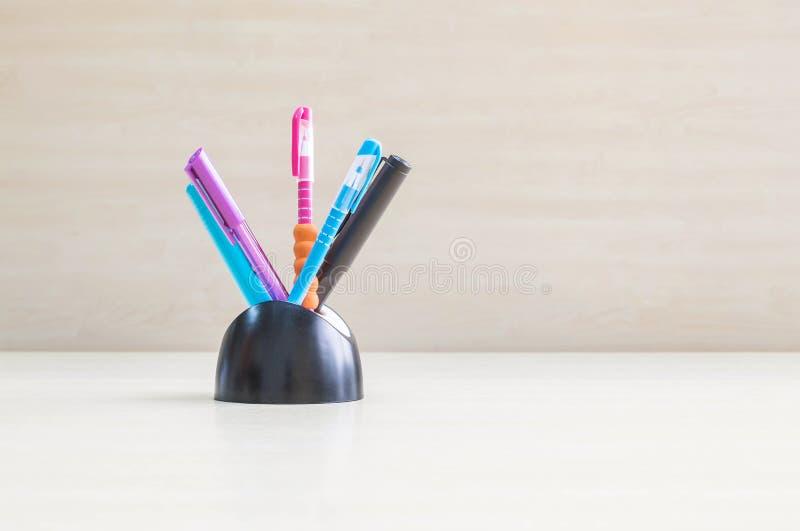 Closeupfärgpennan med det svarta keramiska skrivbordet som var rumsrent för penna på den suddiga wood skrivbord- och träväggen, t royaltyfri fotografi