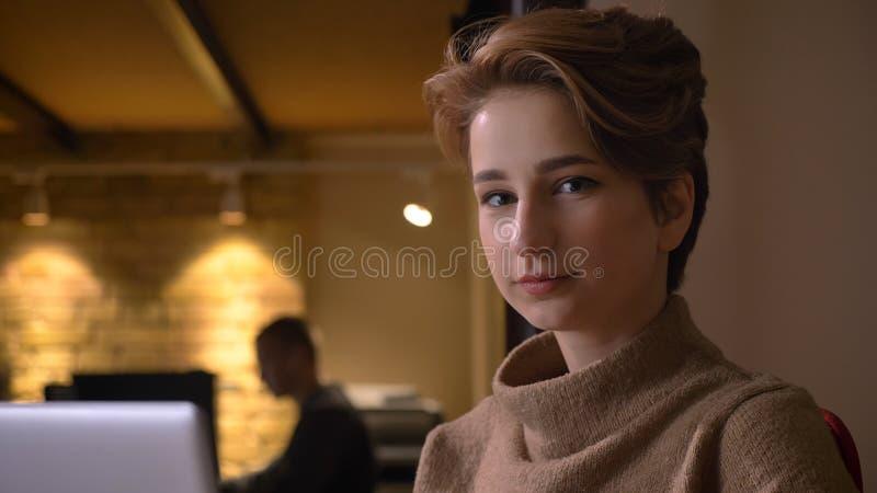 Closeupfors av den unga attraktiva caucasian affärskvinnan som använder bärbara datorn som ser kameran och inomhus ler i royaltyfri bild