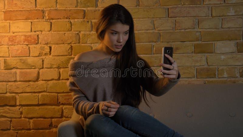 Closeupfors av den unga gulliga caucasian kvinnlign som tar selfies på telefonen med gladlynt ansiktsuttryck, medan vila royaltyfria foton