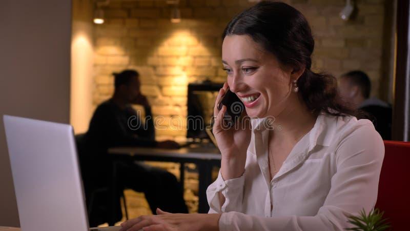 Closeupfors av den unga nätta caucasian affärskvinnan som glatt talar på telefonen, medan sitta framme av royaltyfri foto