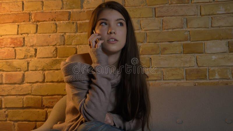 Closeupfors av den unga nätta caucasian kvinnlign som har en tillfällig konversation på telefonen, medan vila på soffan i a fotografering för bildbyråer