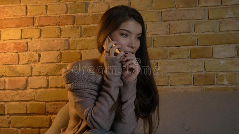 Closeupfors av den unga nätta caucasian kvinnlign som kallar på telefonen med upphetsat ansiktsuttryck, medan vila på arkivbild
