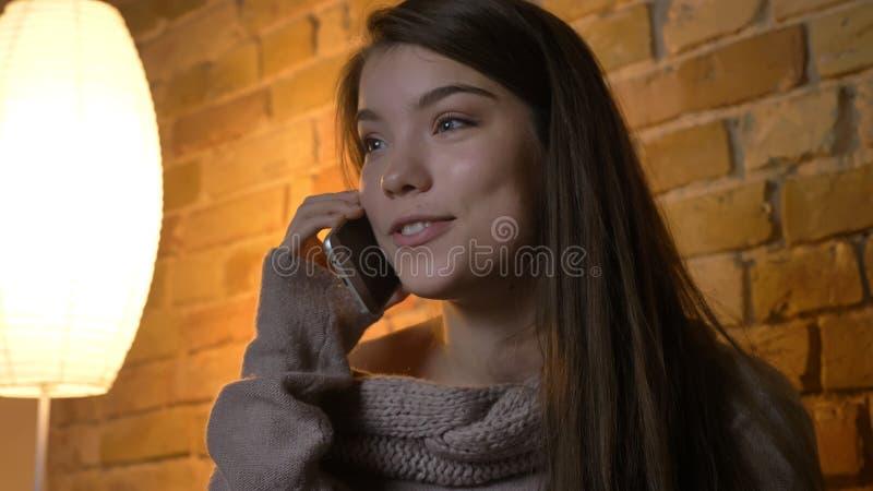 Closeupfors av den unga nätta caucasian kvinnlign som kallar på telefonen och lyckligt ler, medan vila på soffan i a fotografering för bildbyråer
