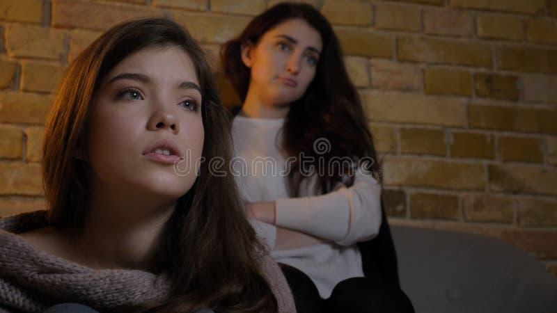 Closeupfors av två unga gulliga flickor som tillsammans håller ögonen på TV och tillsammans spenderar tid, medan vila på soffan i arkivbilder