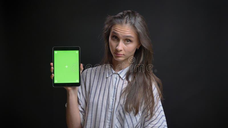 Closeupfors av ungt nätt caucasian kvinnligt smsa på minnestavlan och uppvisning av den gröna skärmen till kameran med isolerat royaltyfri bild