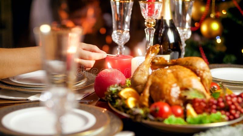 Closeupfoto av att tända upp stearinljus på julmatställetabellen mot den brinnande spisen royaltyfria bilder