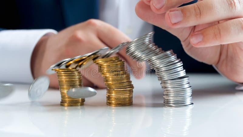 Closeupfoto av buntar av mynt som faller på det vita träkontorsskrivbordet finansiell begreppskris royaltyfria foton