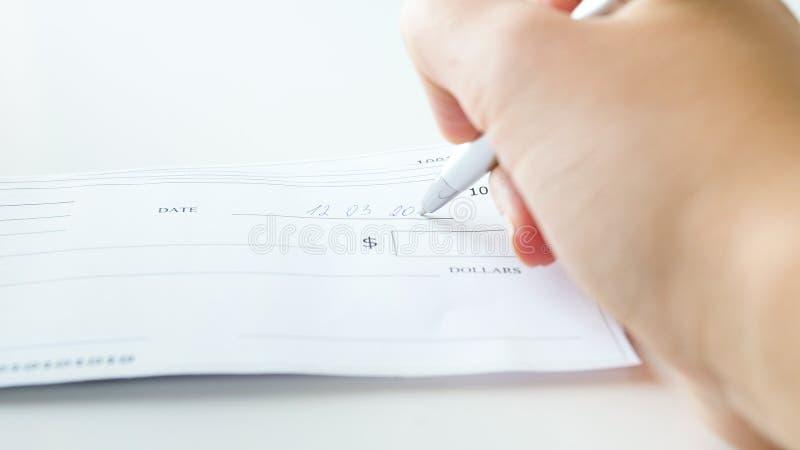 Closeupfoto av den fyllnads- bankrörelsechecken för ung kvinna med pennan fotografering för bildbyråer