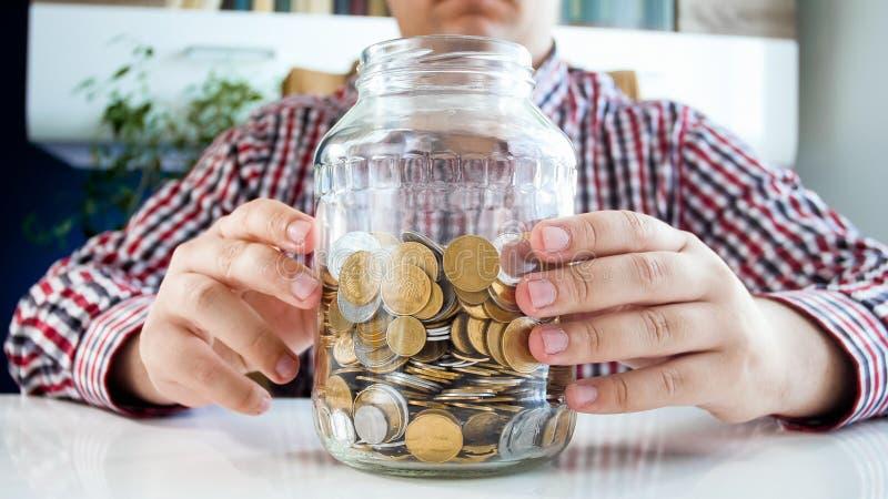 Closeupfoto av den hållande glass kruset för ung man som är full av mynt, begrepp av rikedom och rikedom royaltyfri foto