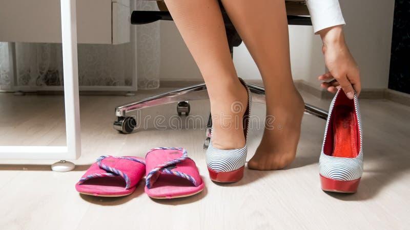 Closeupfoto av den unga affärskvinnan i strumpbyxor som tar skor för höga häl och bär bekväma hem- häftklammermatare royaltyfri bild