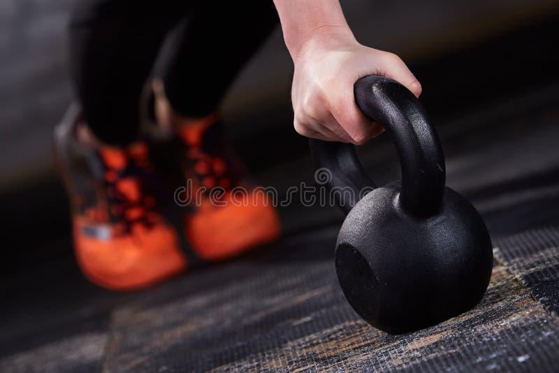 Closeupfoto av den unga kvinnan i den svarta damasker och de orange sneackersna medan push-UPS med kettlebell royaltyfri fotografi