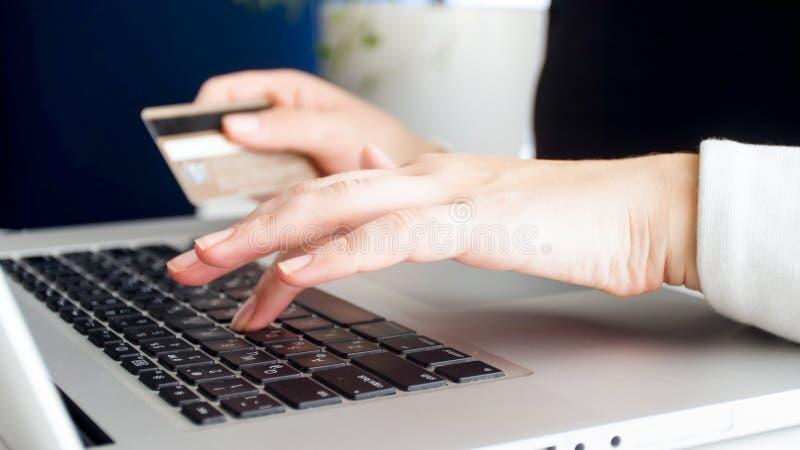 Closeupfoto av den unga kvinnan som betalar online-köp med kreditkorten royaltyfri bild