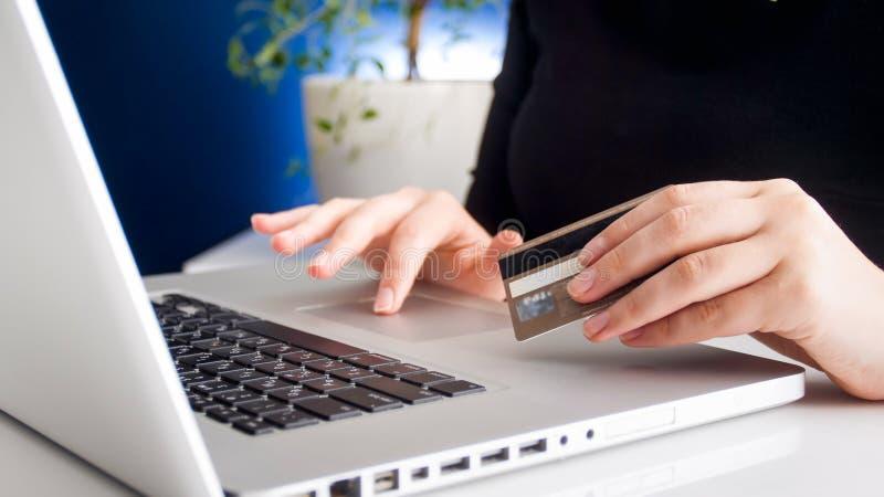 Closeupfoto av den unga kvinnan som gör onkineshopping- och innehavkreditkorten royaltyfri fotografi