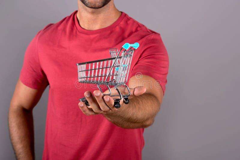 Closeupfoto av en mini- shoppa vagn medan en man som rymmer den fotografering för bildbyråer
