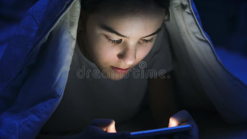 Closeupfoto av flickan i pyjamas som bläddrar internet på smartphonen under filten på natten royaltyfri foto