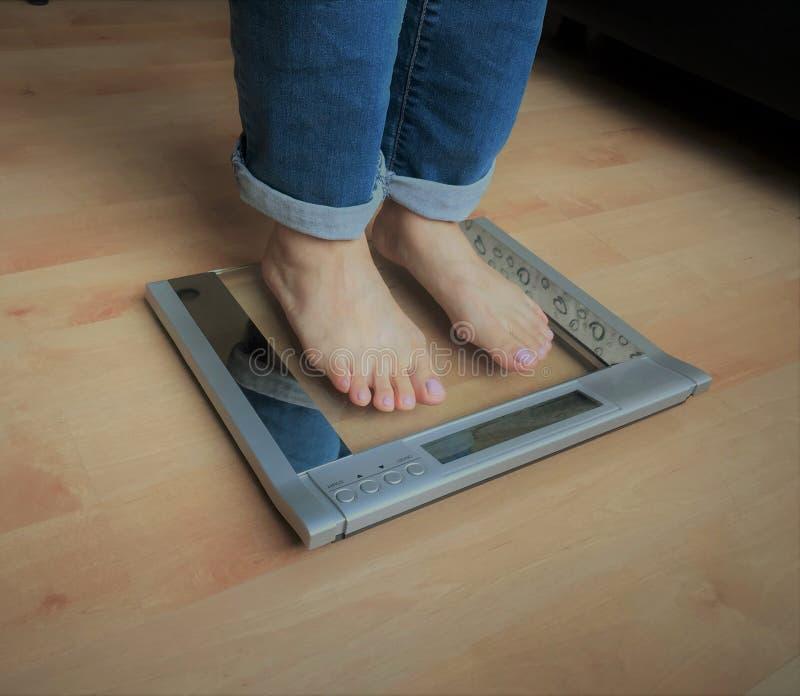 Closeupfoto av fot för kvinna` som s står på viktsacle över ädelträgolvet arkivfoton
